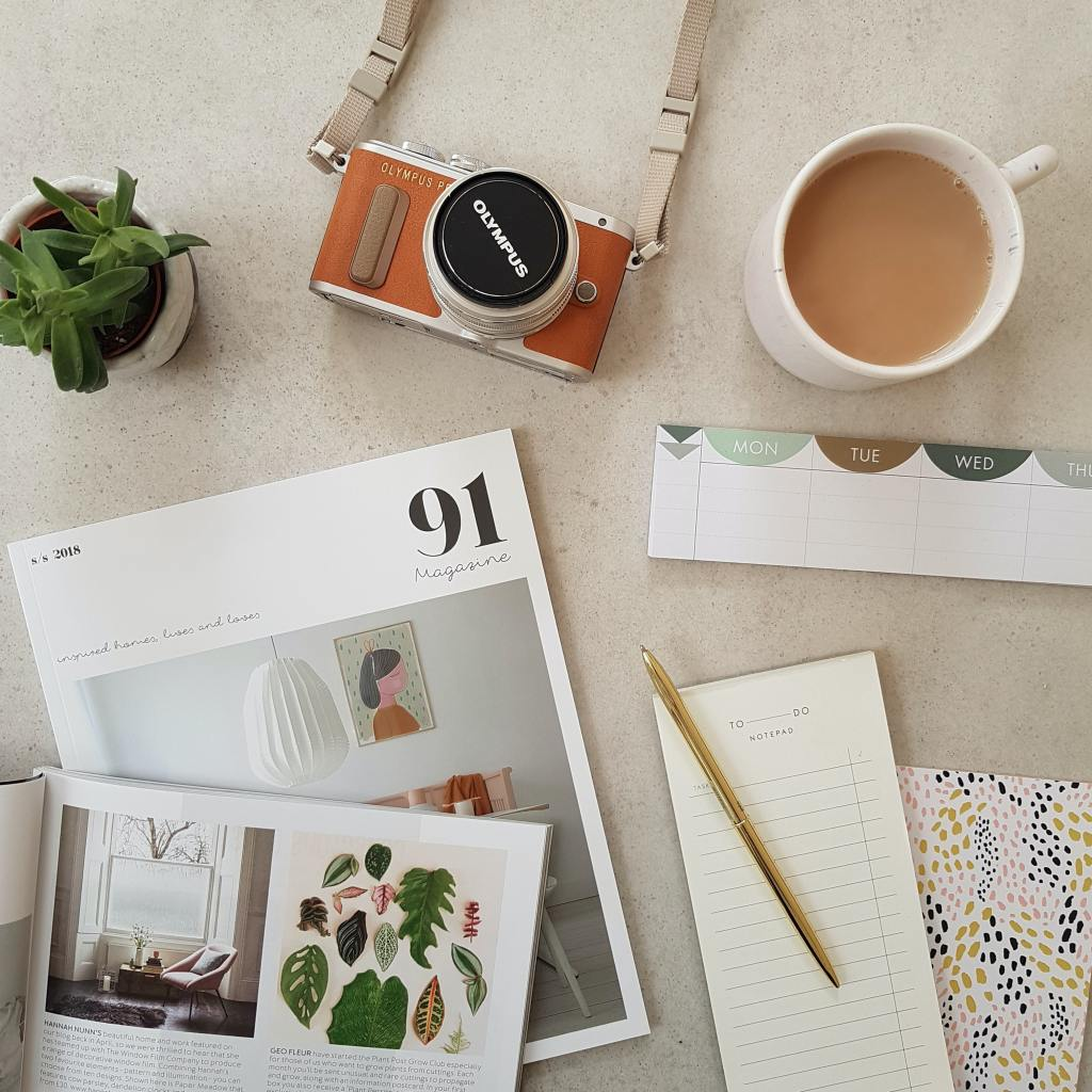 Blog post research material shown in flat lay with a small plant, writing tools and a cup of copy