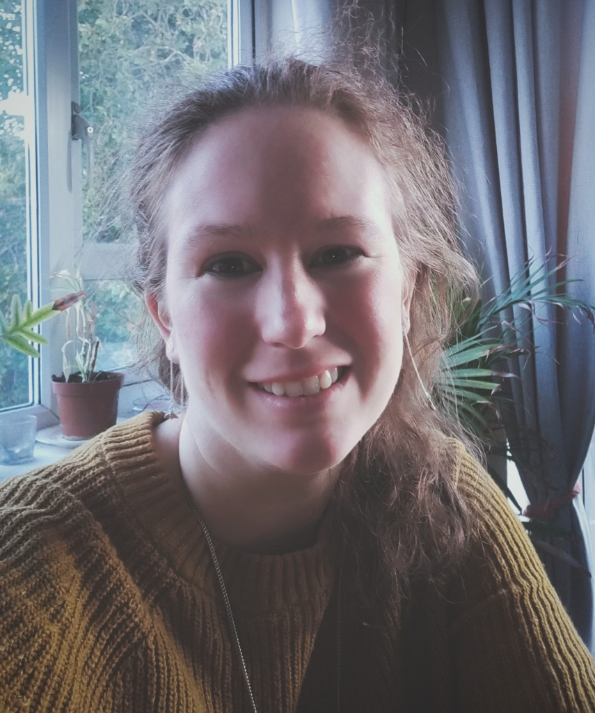 Lucy, a freelance writer, smiling in front of a window. She dark red hair and a mustard yellow jumper